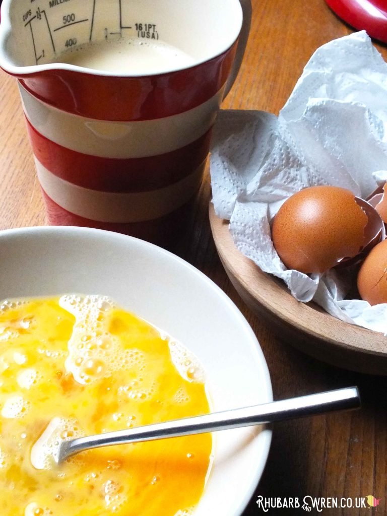 bowl with beaten eggs, jug with milk