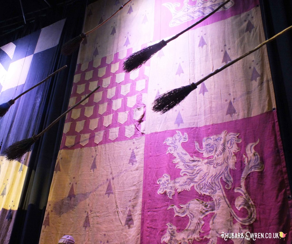 Broomsticks flying in front of a gigantic banner at the Harry Potter studio tour, UK.