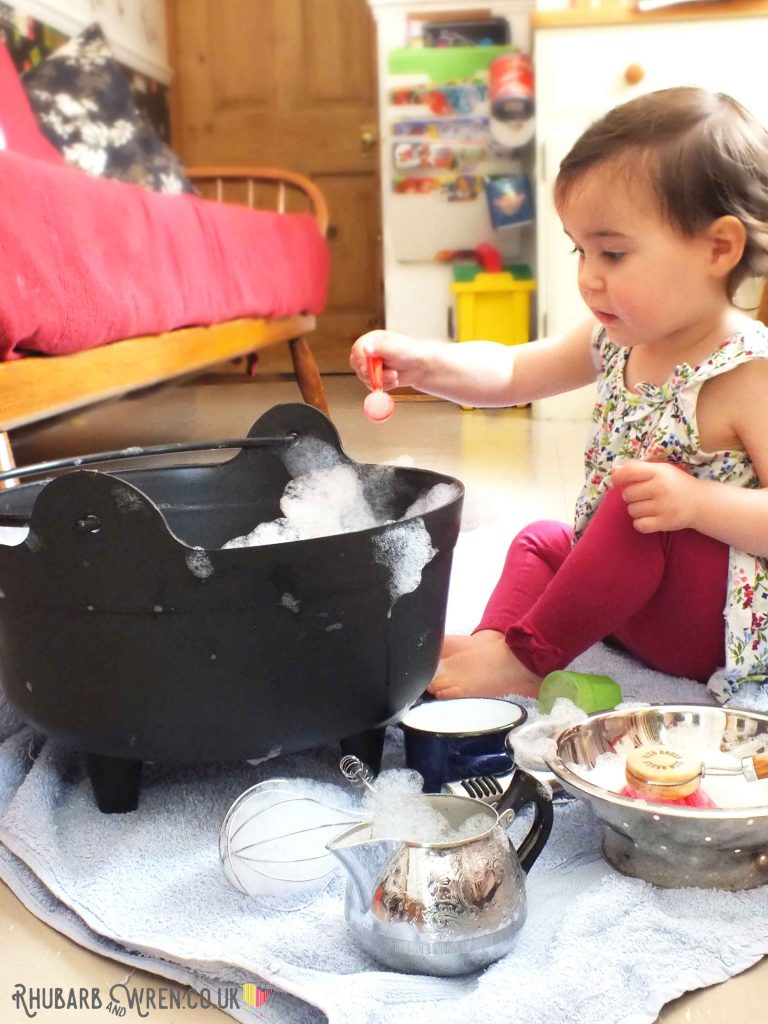 toddler playing with bubbles and kitchen utensils