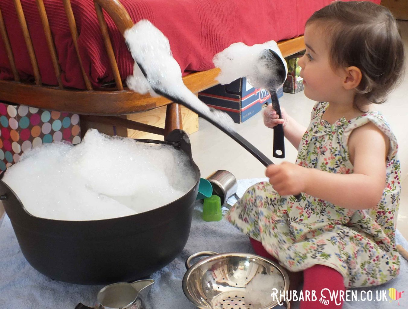 toddler with kitchen utensils and bowl of bubbles - bubble play