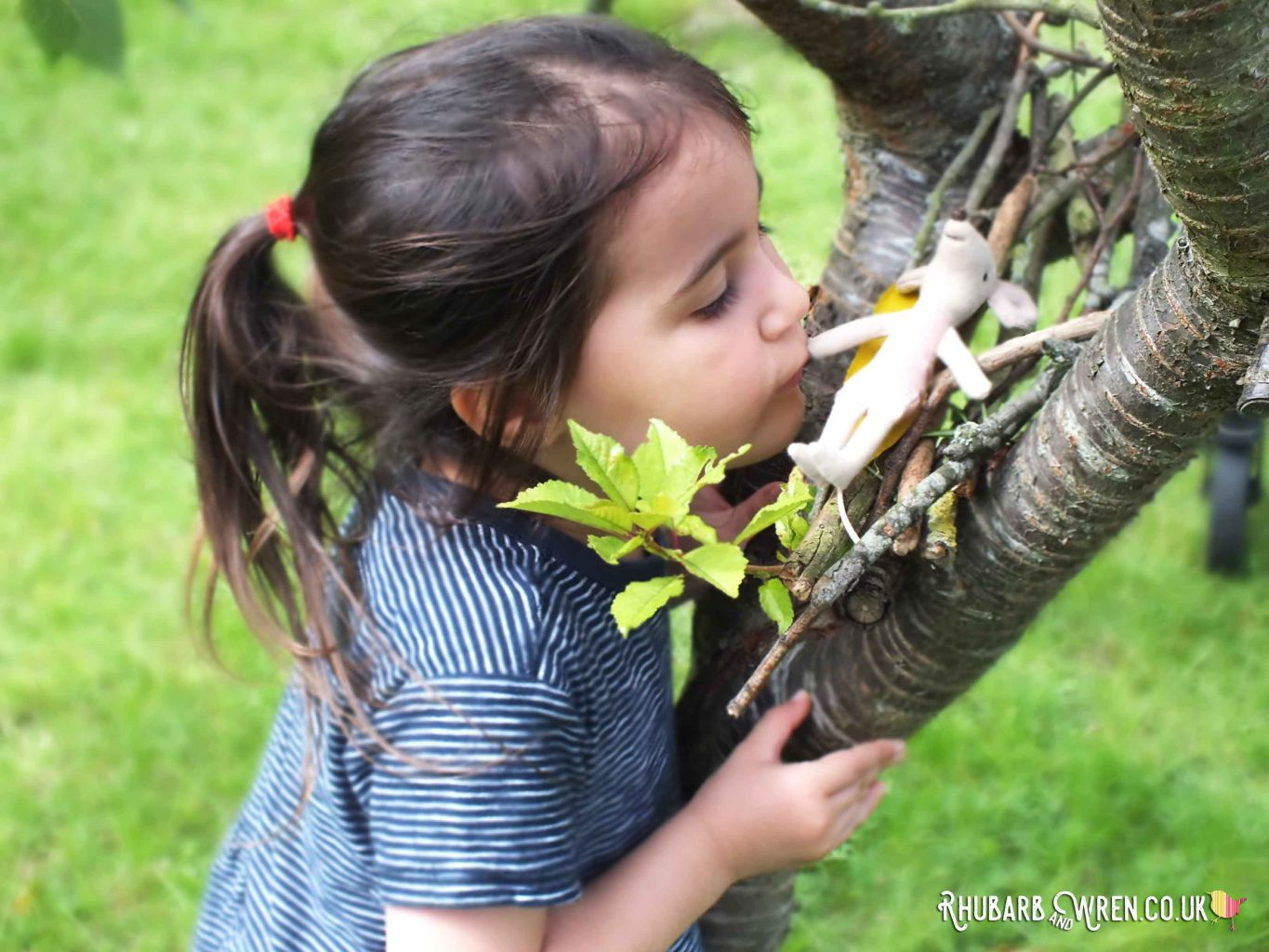 Girl kissing Maileg mouse toy in tree