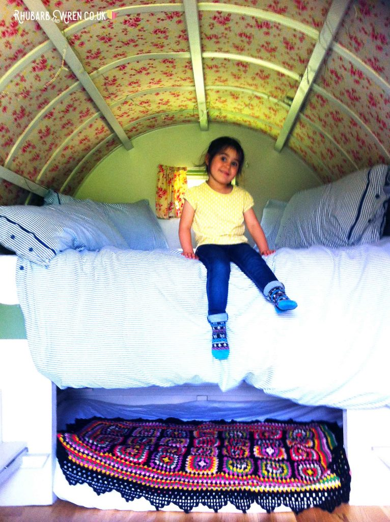 Girl sitting on bed in gypsy caravan at Farrs Meadow, Dorset