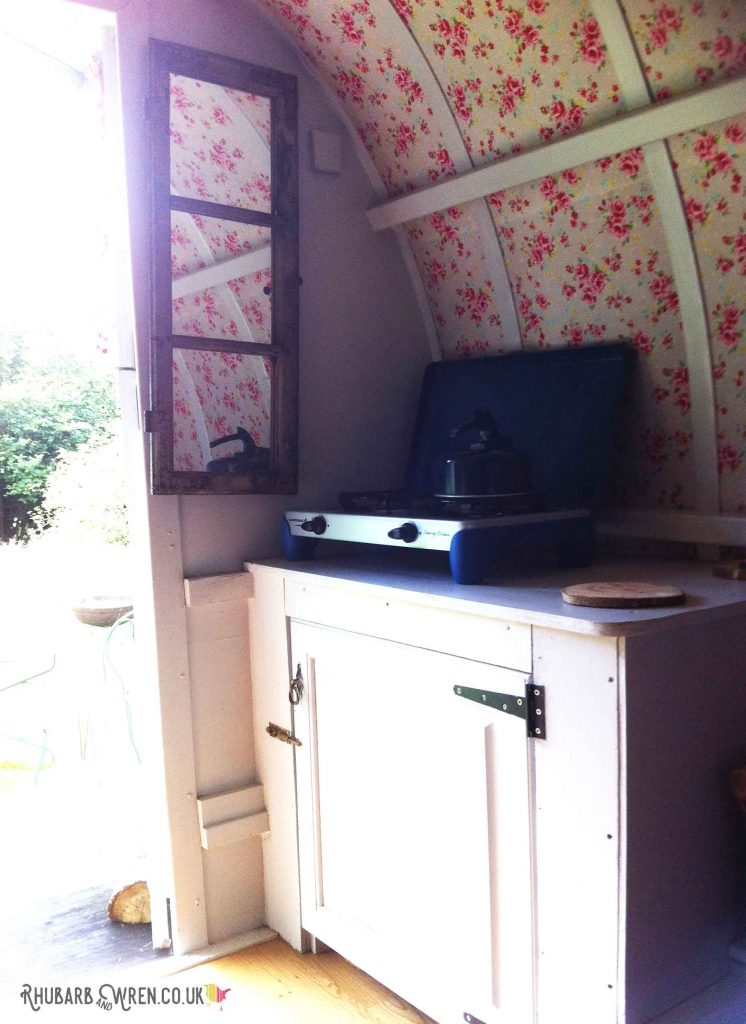 Cupboard and camping stove inside gypsy caravan at Farrs Meadow, Dorset