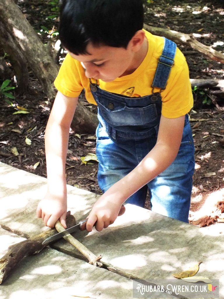 Boy cutting stick with saw at woodland worktable
