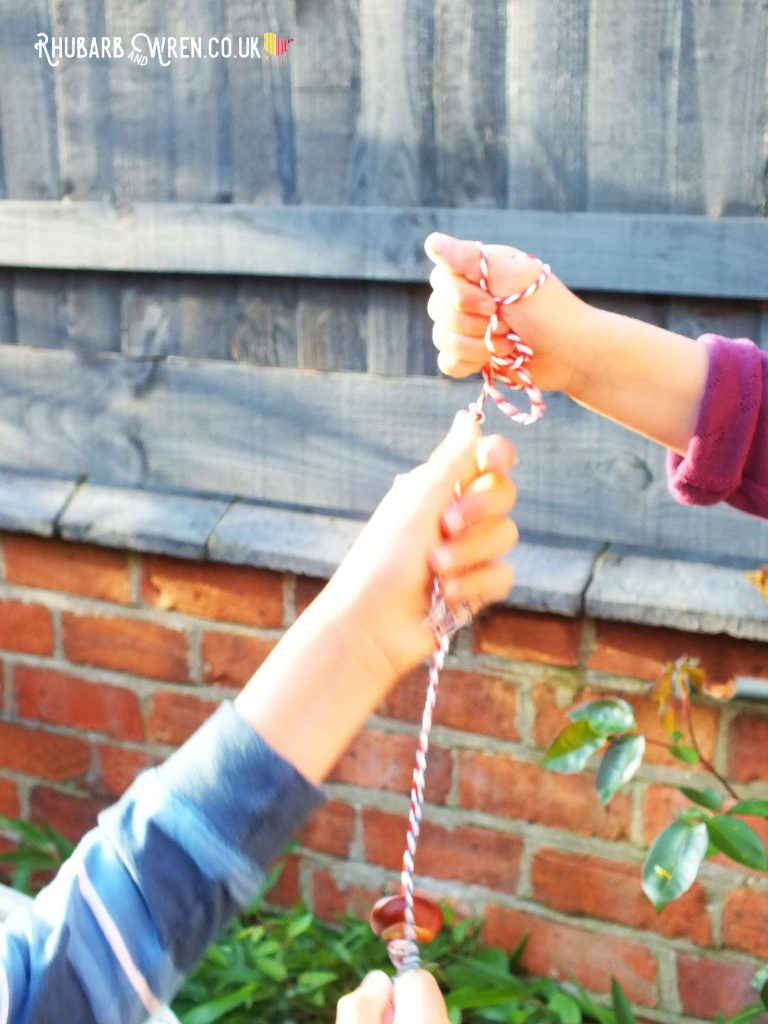 Children holding conkers on string