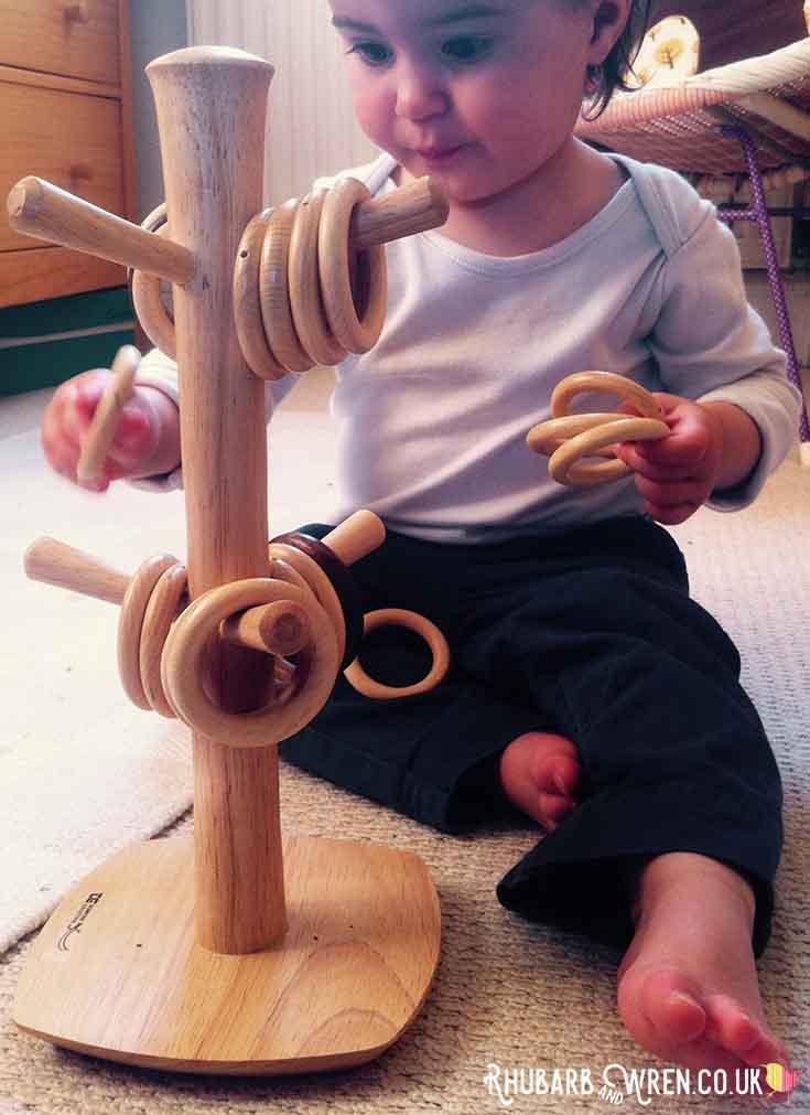 Baby putting wooden rings onto mug tree - making a 'hoop tree'