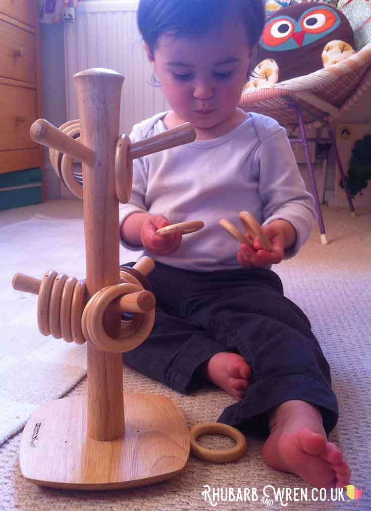 baby looking at wooden rings and hanging them on a mug tree