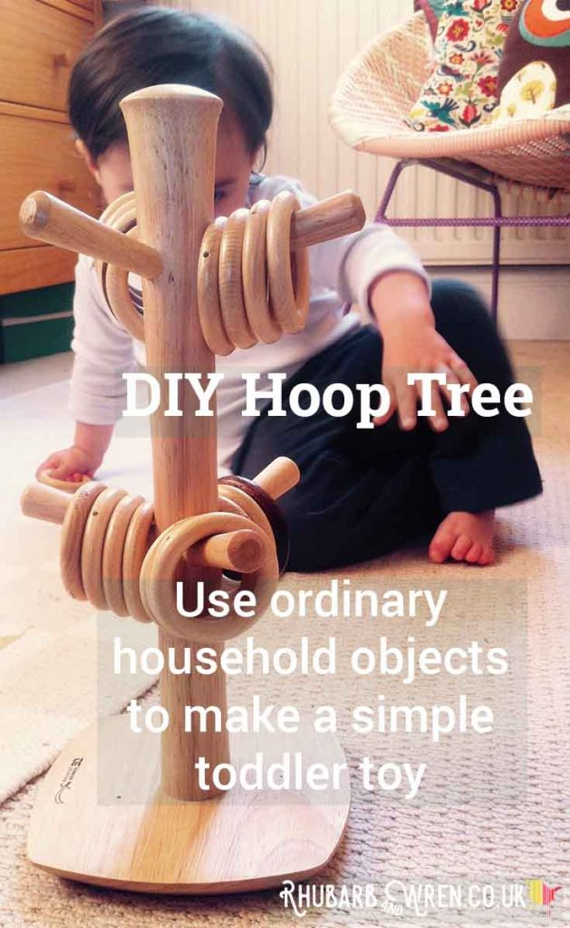 Baby playing with mug tree covered in wooden rings