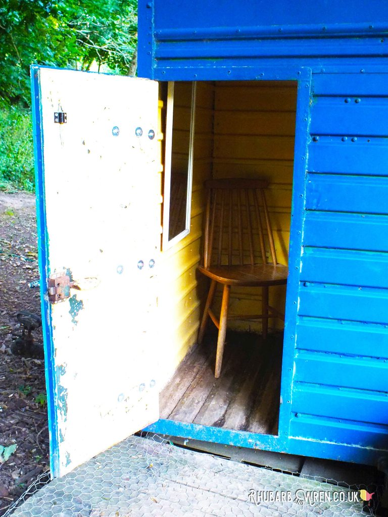 Open door to converted horse box shower at Farrs Meadow campsite, Dorset, UK
