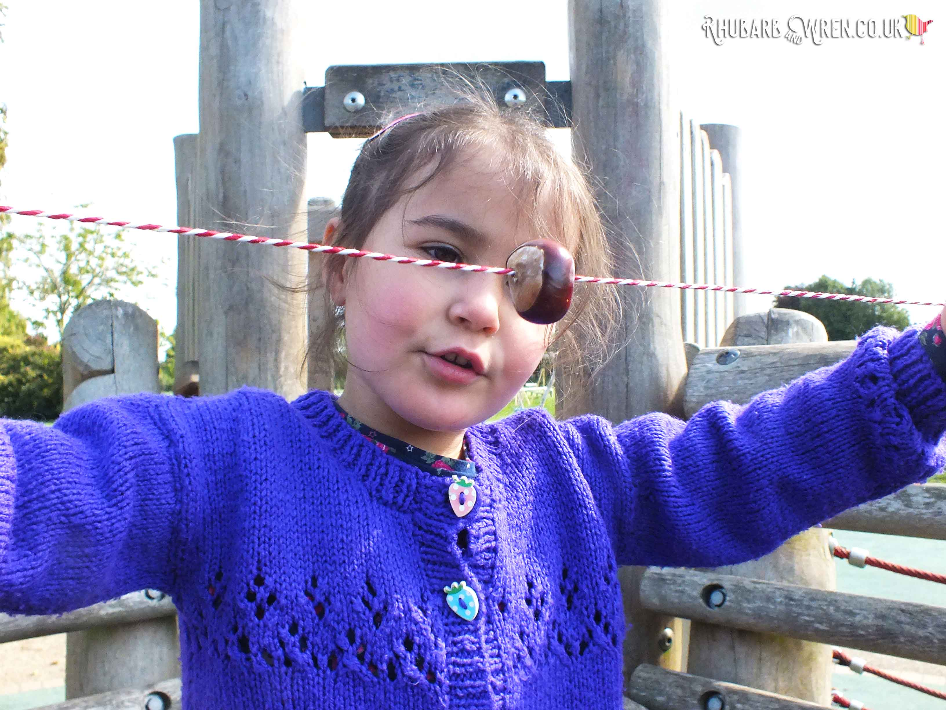 girl displaying conker threaded onto string.