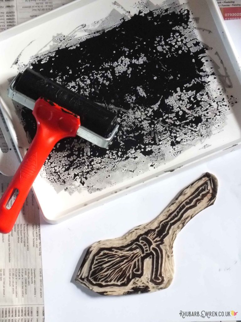 Ink on ink tray, brayer or roller, and inked-up lino cut of Harry Potter's Firebolt broomstick