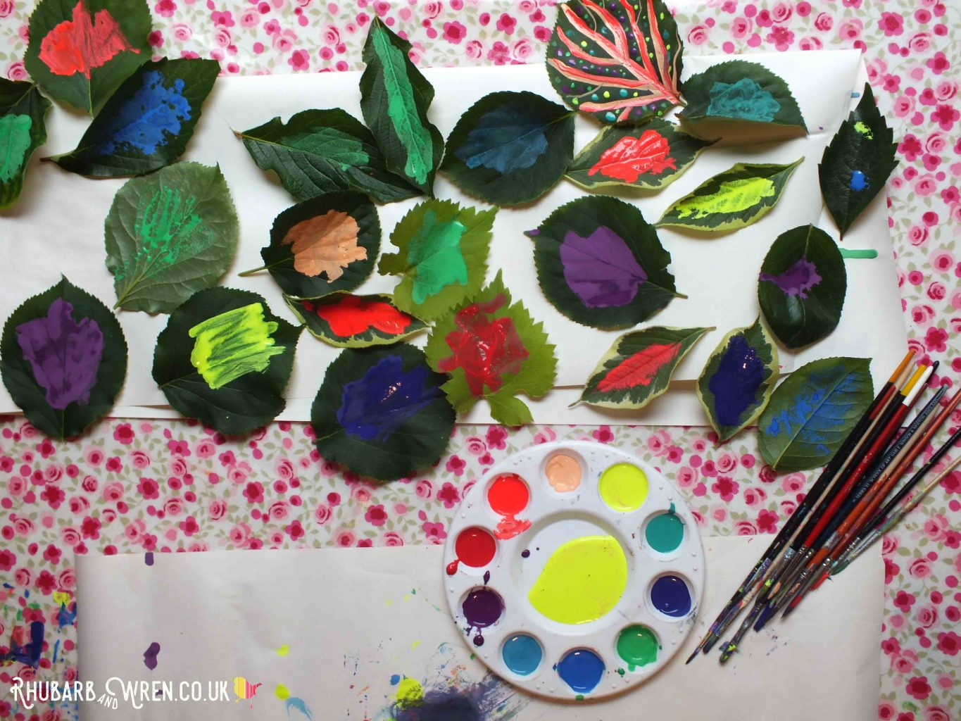 Painted leaves and round pallet with rainbow of paint, and paintbrushes.