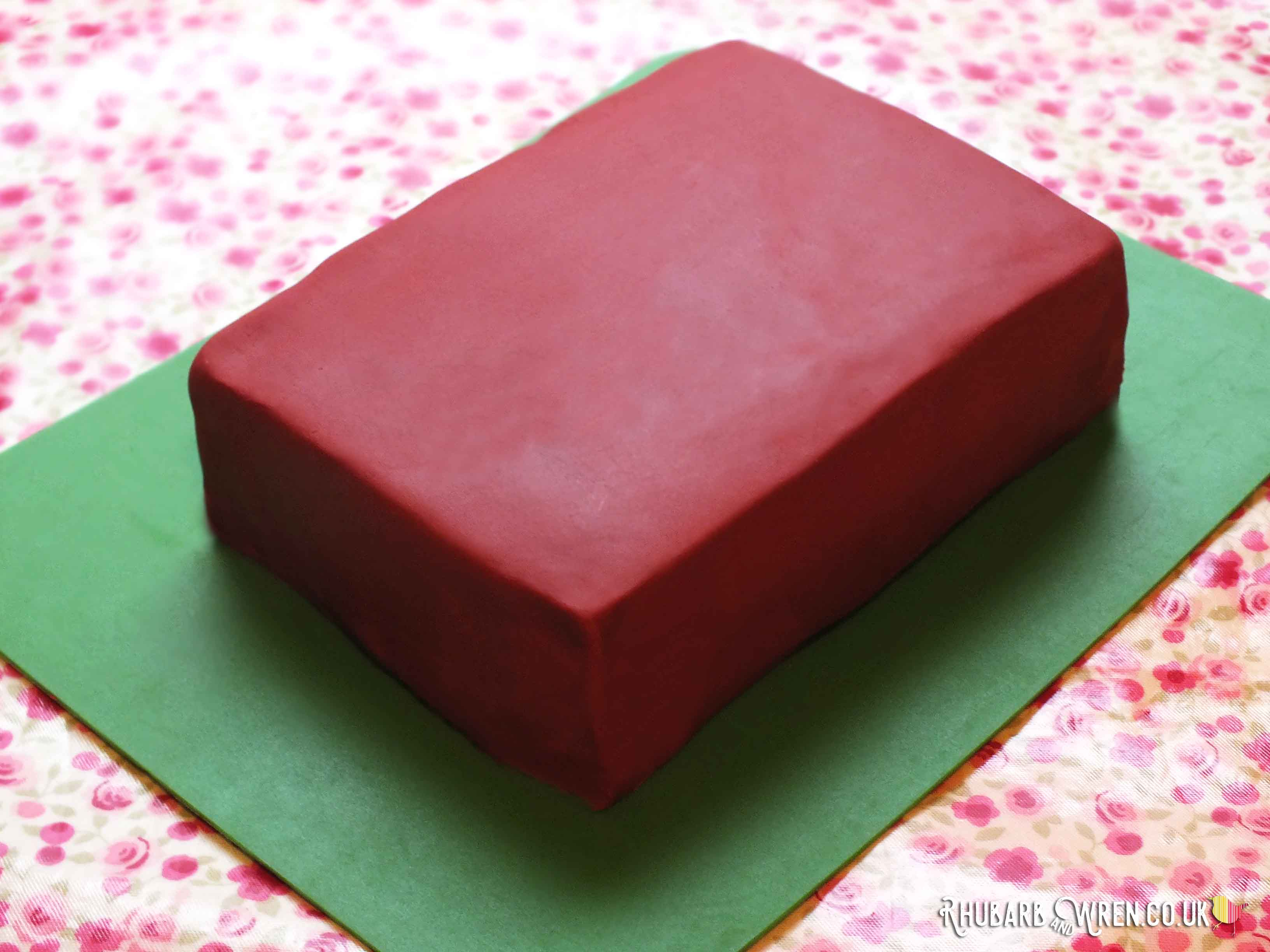 Rectangular cake covered in red fondant icing