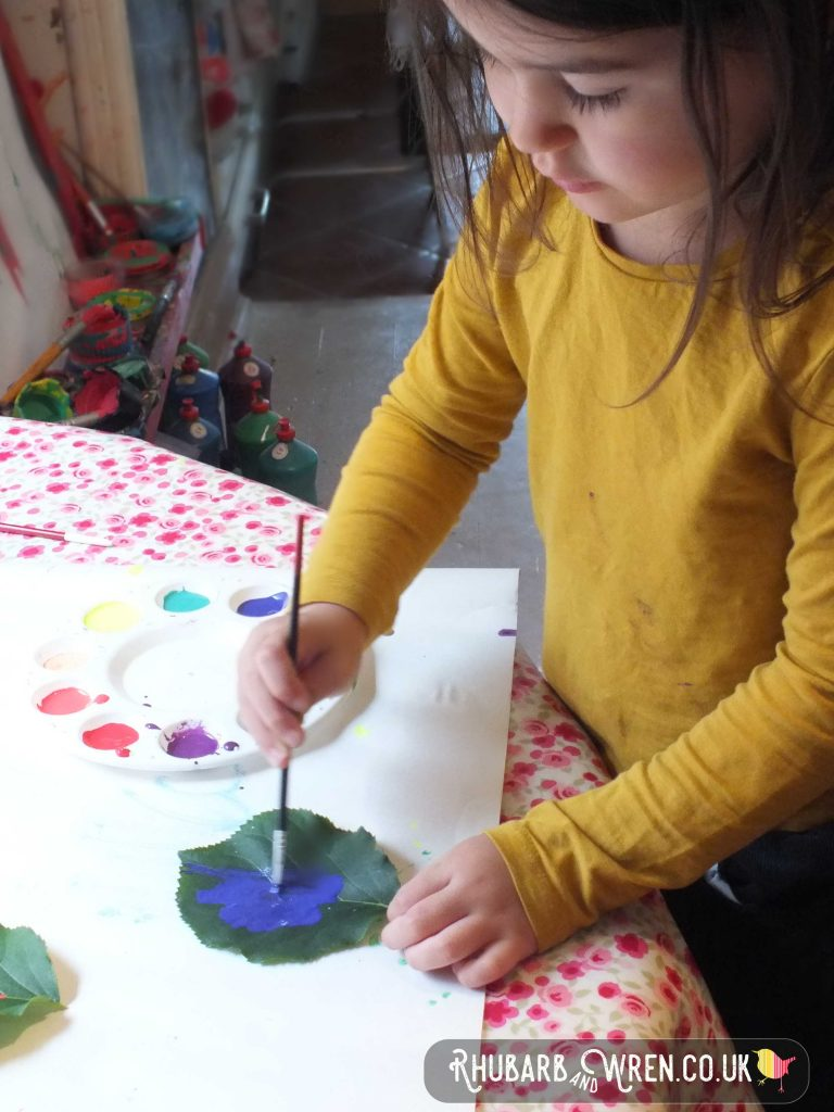 Child painting a leaf with purple paint