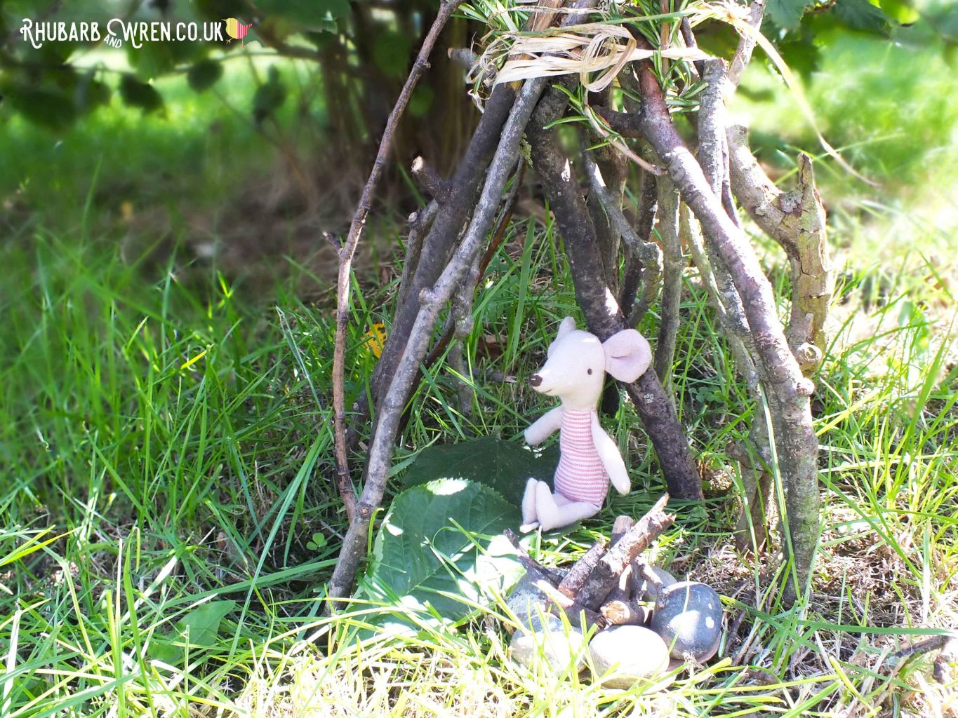 Maileg mouse toy sitting in mini twig teepee with mini campfire