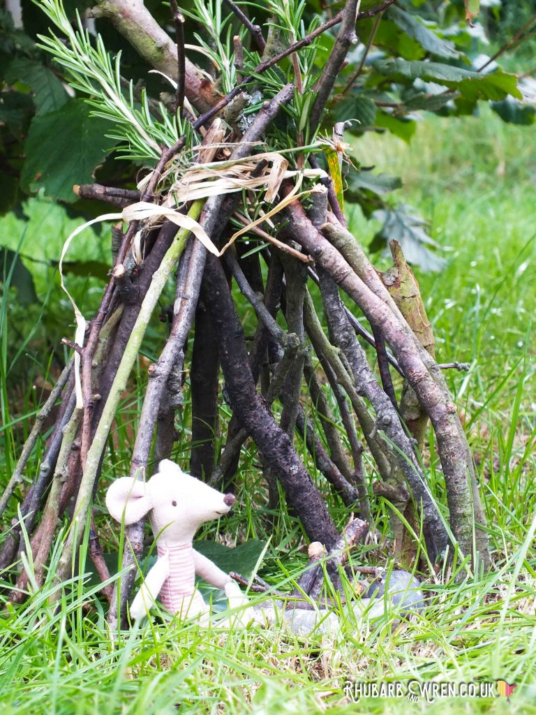 Maileg mouse toy sitting in twig teepee in meadow
