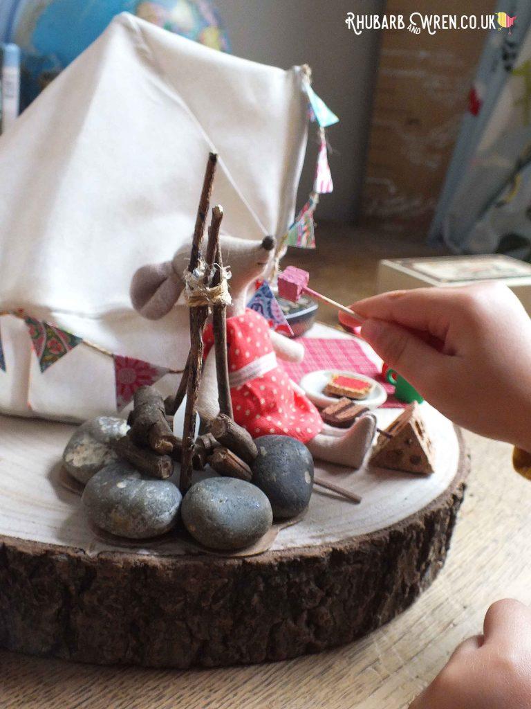 Child's hand feeding mini marshmallows to Maileg mouse