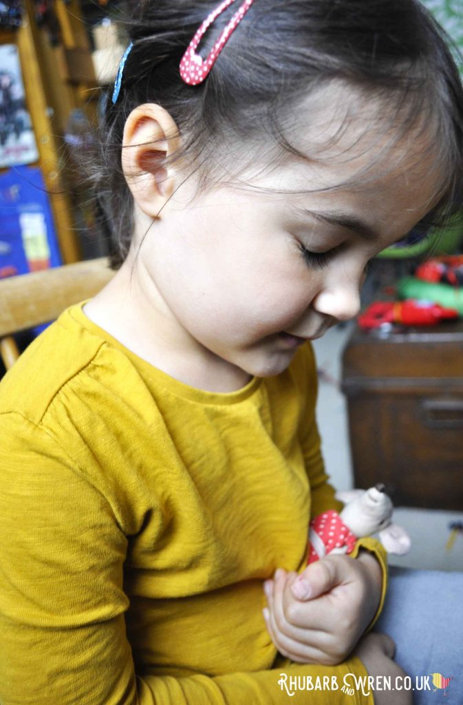 Little girl cuddling toy maileg mouse Big Sister