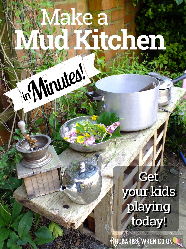 Child's mud kitchen with bow of flowers, saucepan and teapot.