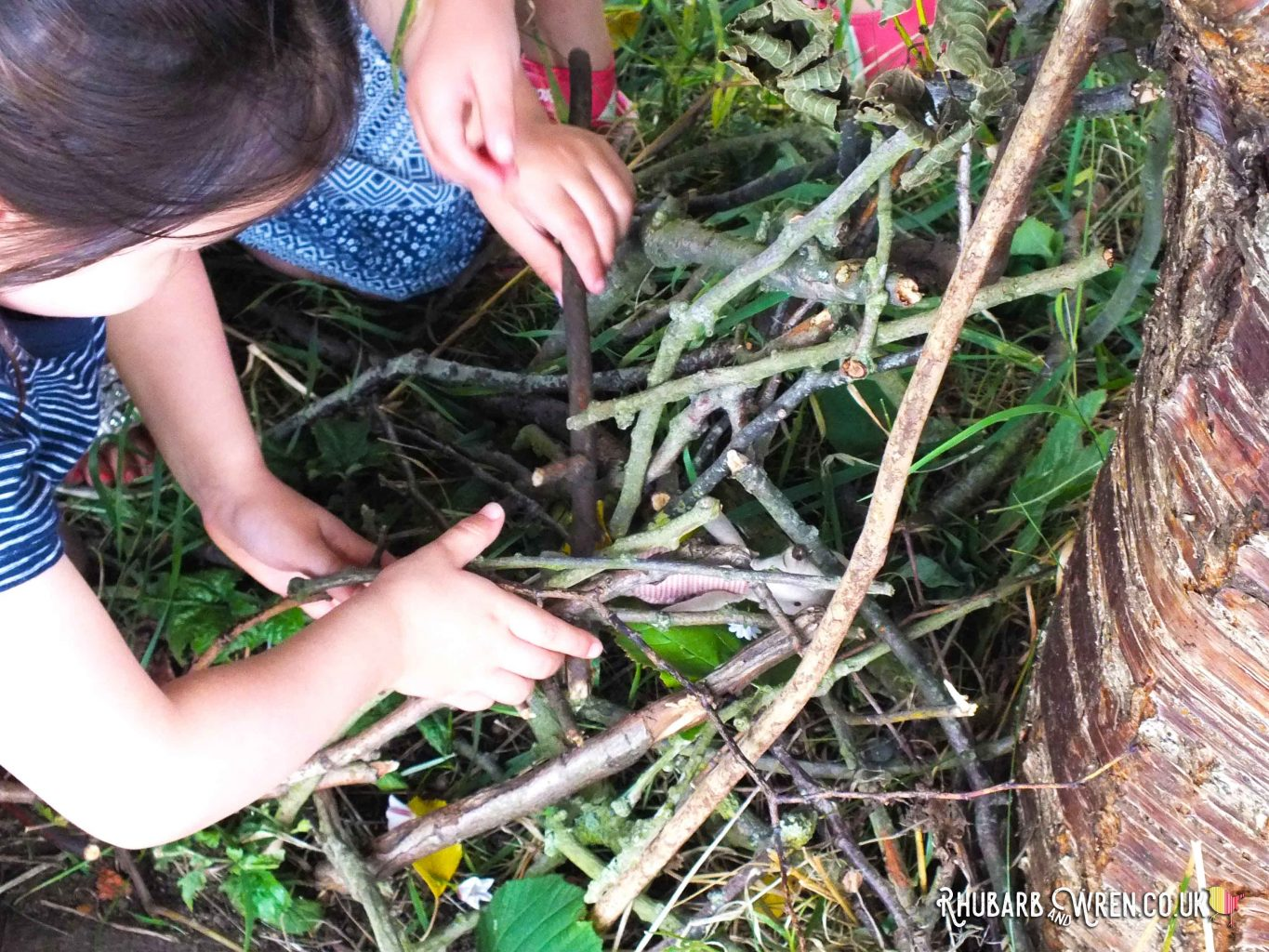 children building mini den out of twigs