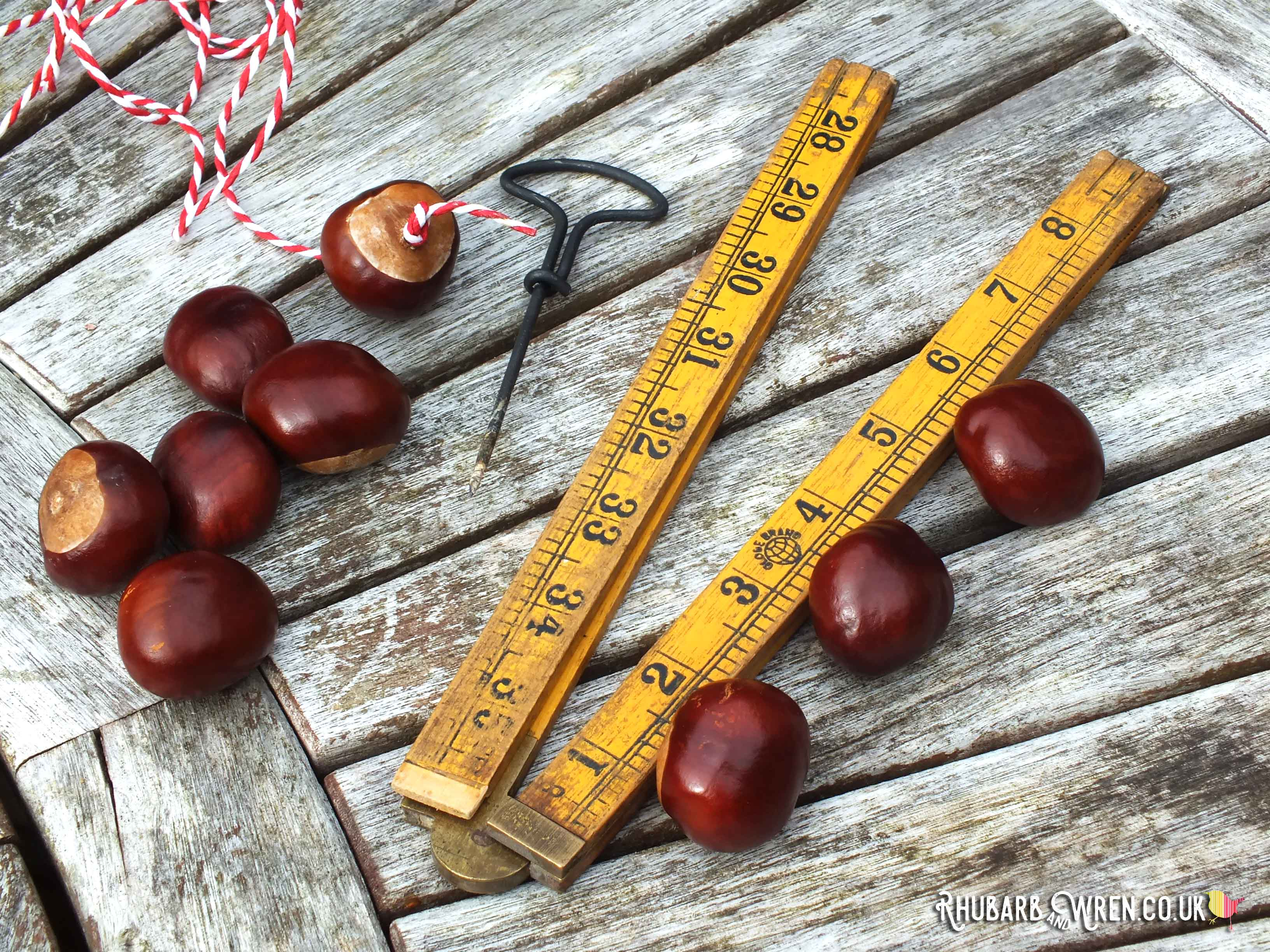 conkers scattered on table with hand drill and folding ruler