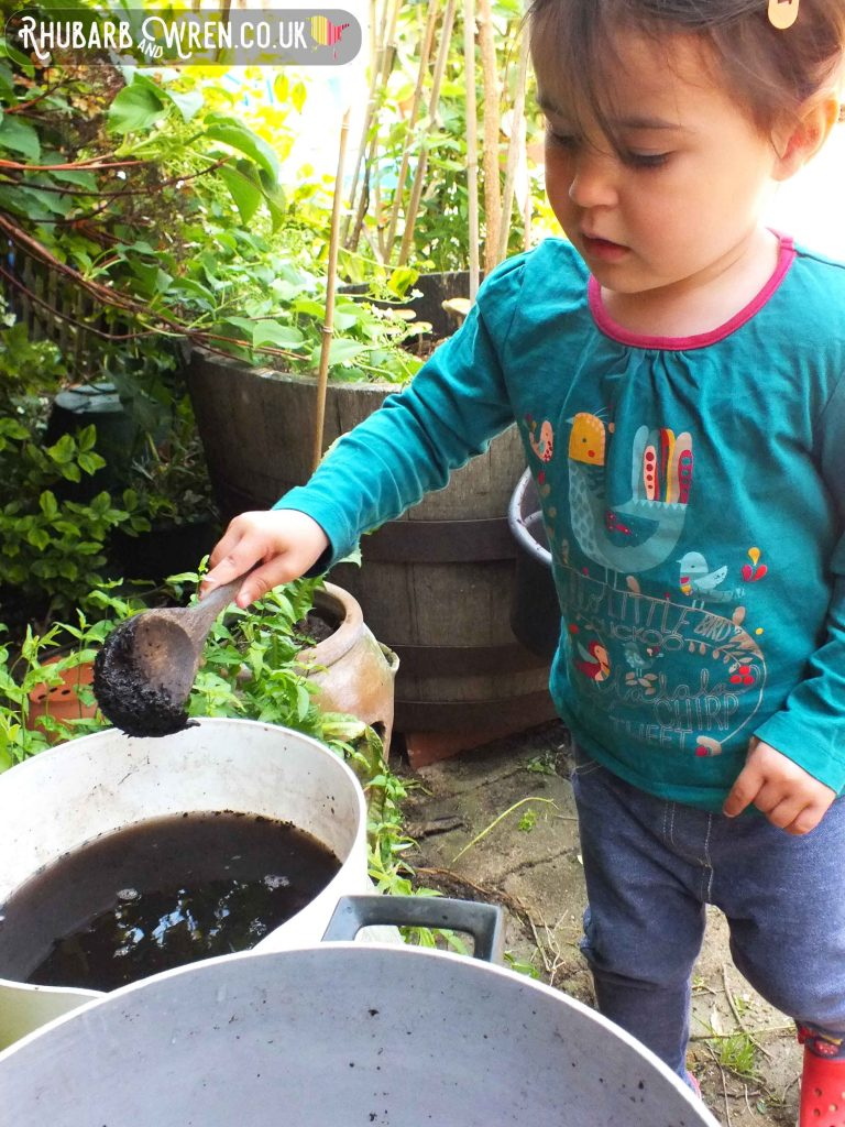 little girl mixing mud soup in a mud kitchen