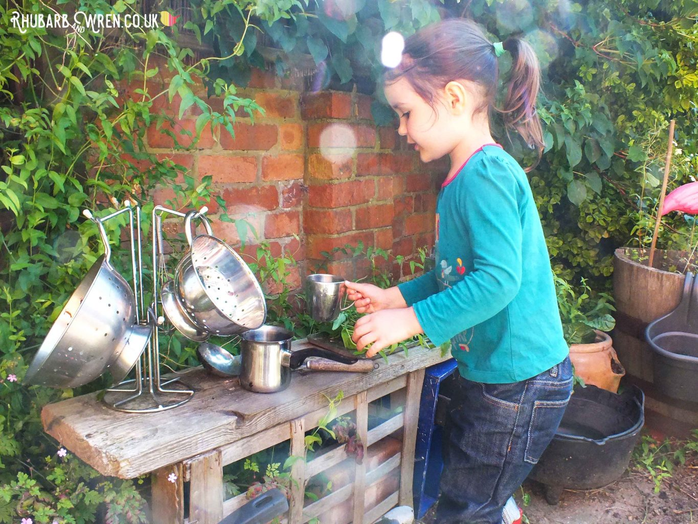 little girl cooking in a mud kitchen