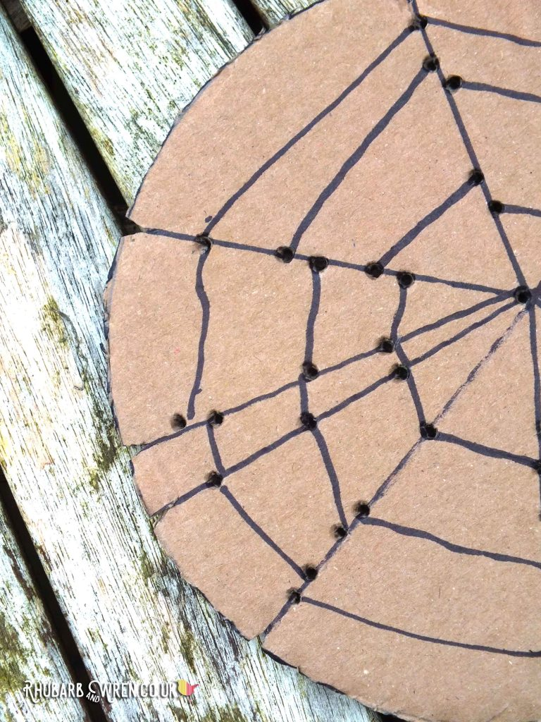 Close-up of spiderweb drawn on cardboard circle - holes punched for threading, and notches cut at edges to hold string in place.