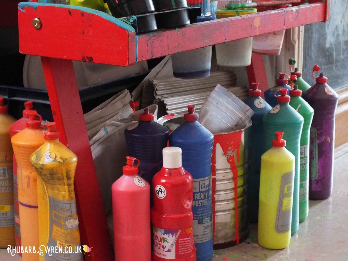 colourful bottles of paint stood under child's easel