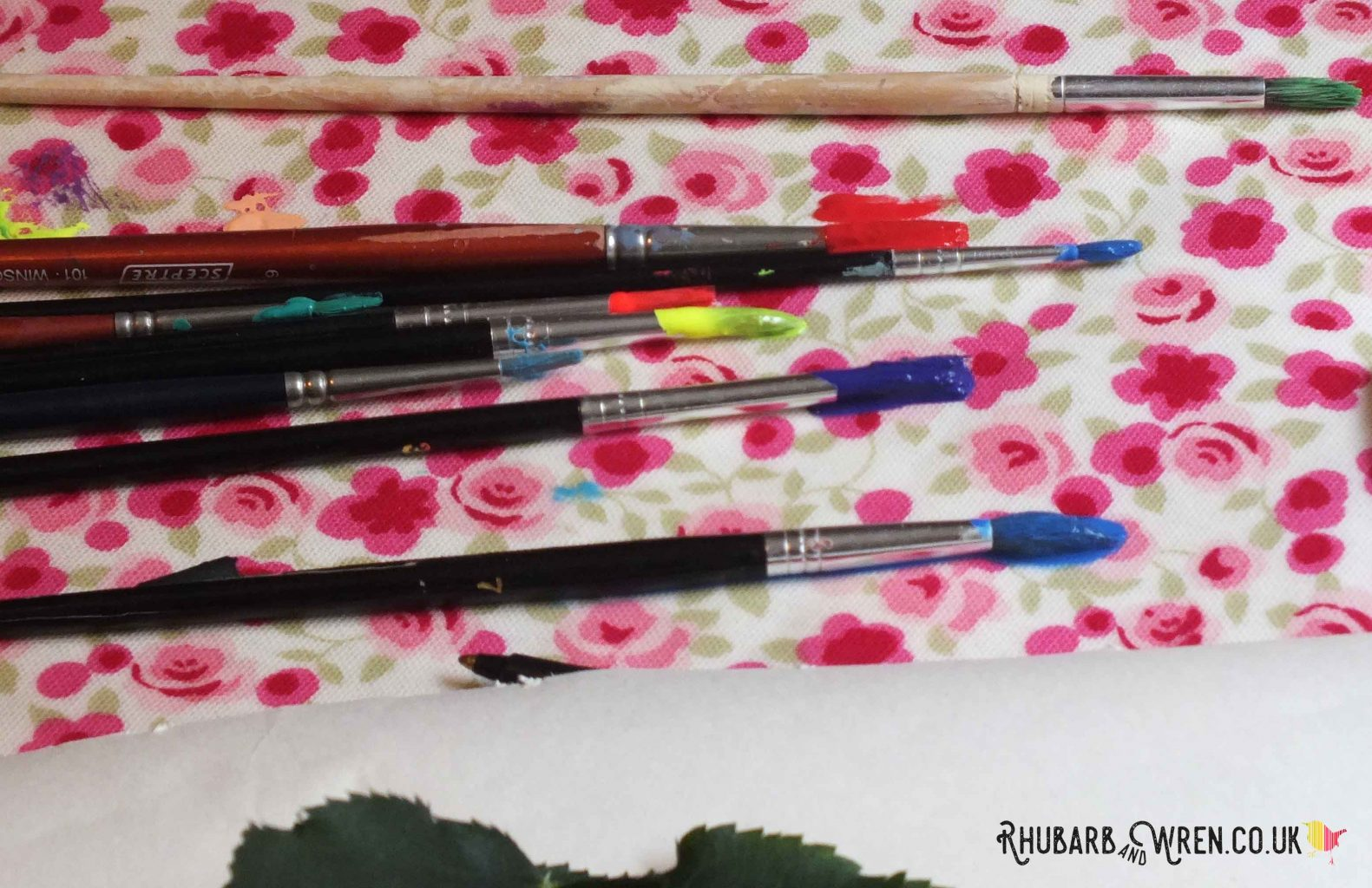 paintbrushes with bright paint on bristles