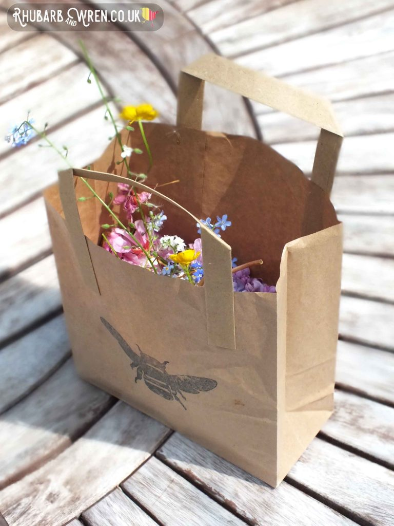paper bag with bee printed on it, full of hedgerow wild flowers