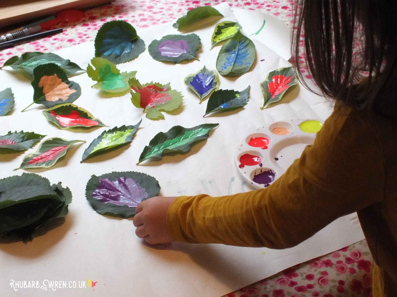 child arranging painted leaves on big sheet of papaer