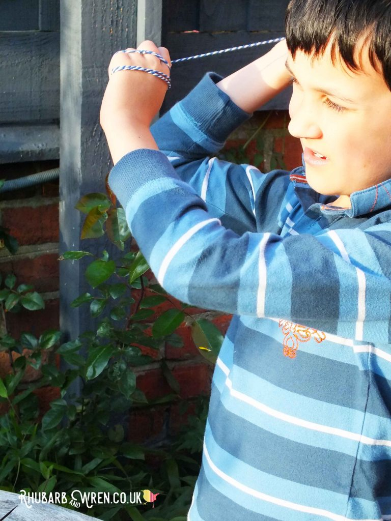 Boy playing conkers poised to swing conker on string