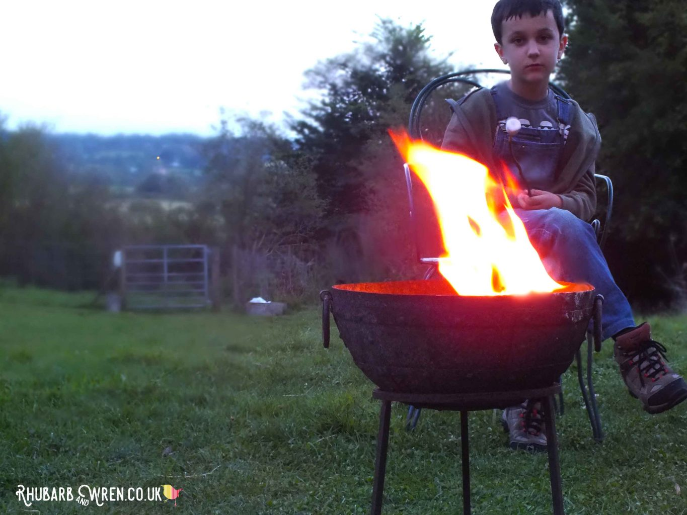 Boy sitting by campfire at dusk, Farrs Meadow, Dorset, UK