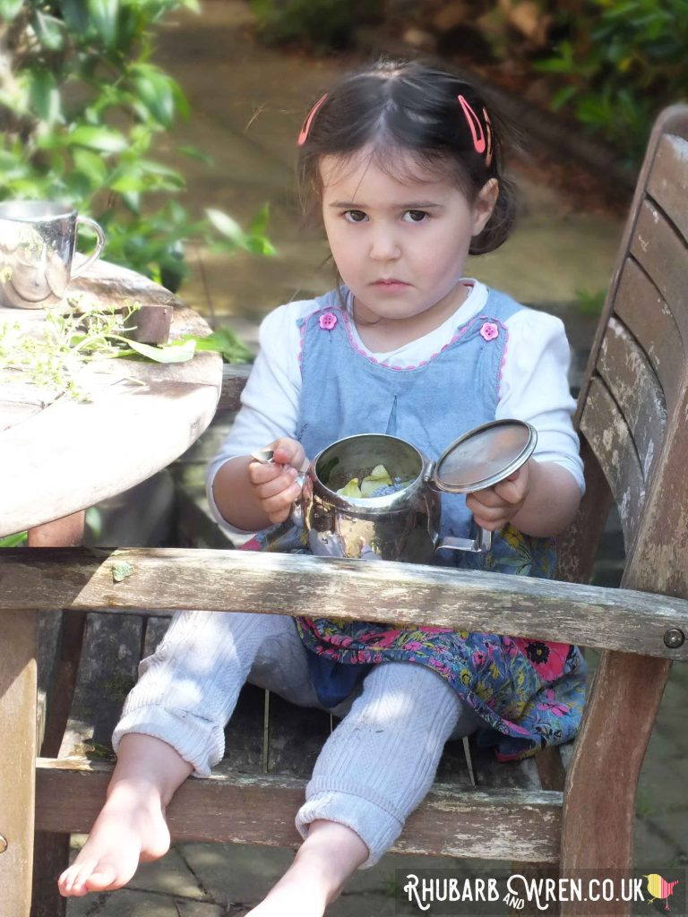 child looking in empty teapot in garden