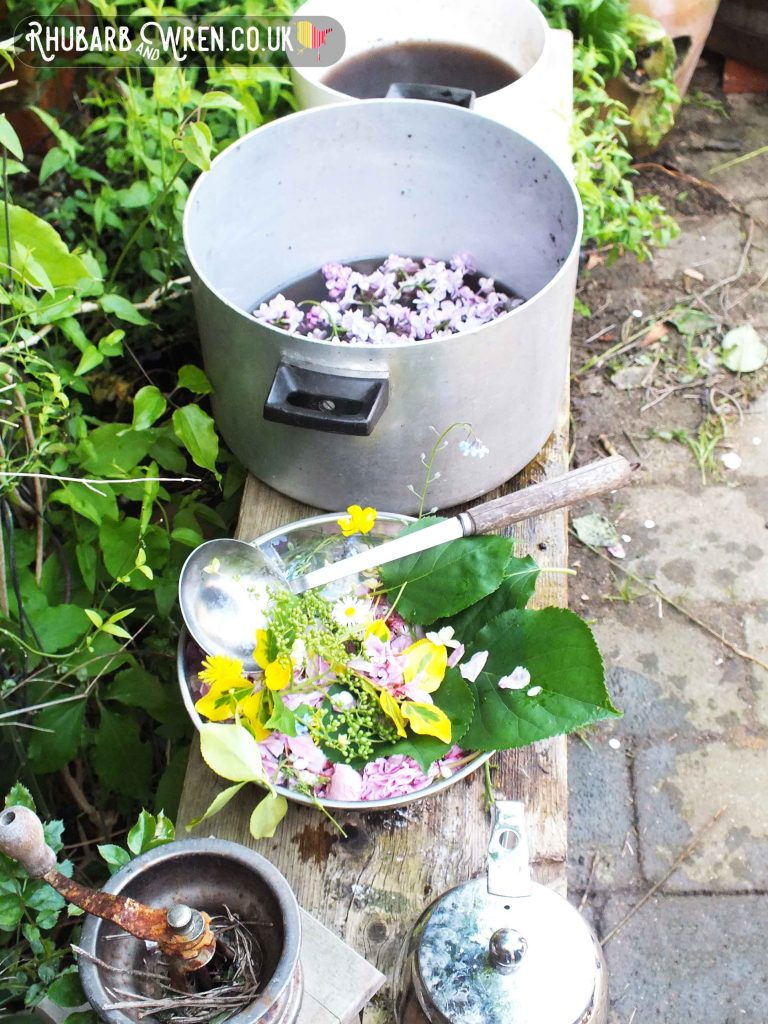 Mud kitchen with saucepans and bowls full of colourful flowers, water and mud