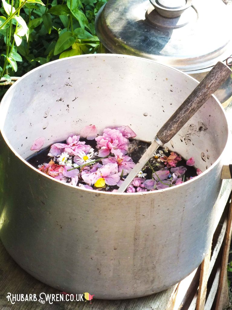 Big saucepan from mud kitchen full of muddy water and pretty pink blossom