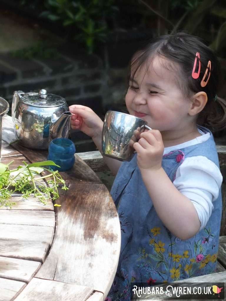 child drinking pretend tea in the garden.