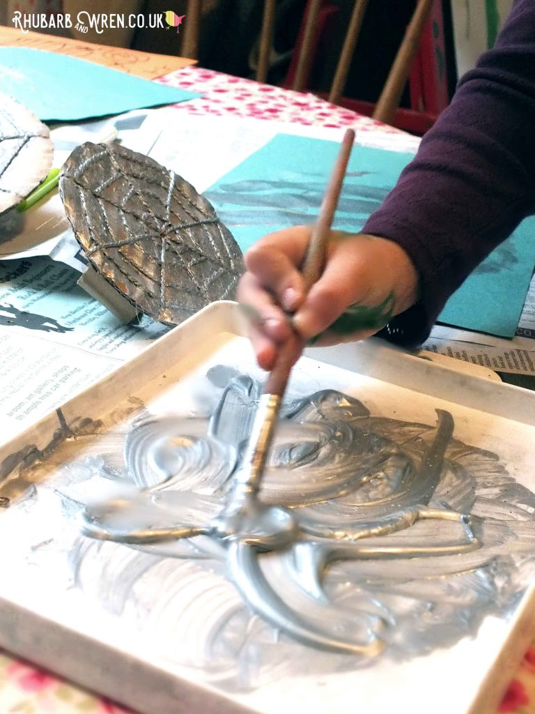 Child using paintbrush to mix silver paint