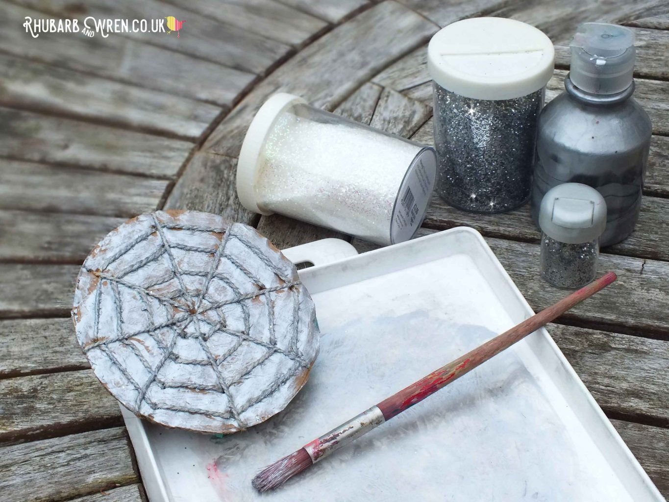 Spiderweb stamper covered in silver paint, with jars of glitter next to it.