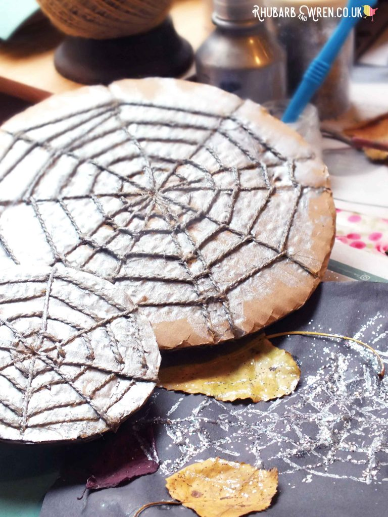 Cardboard and string spiderweb stampers, covered in silver paint.
