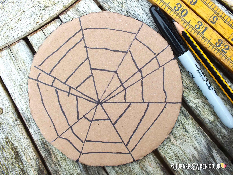 Spiderweb drawn onto a circle of corrugated cardboard