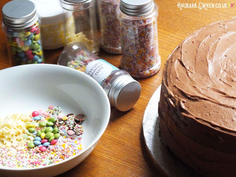 iced chocolate cake, bowl of cake sprinkles with jars of sprinkles behind.