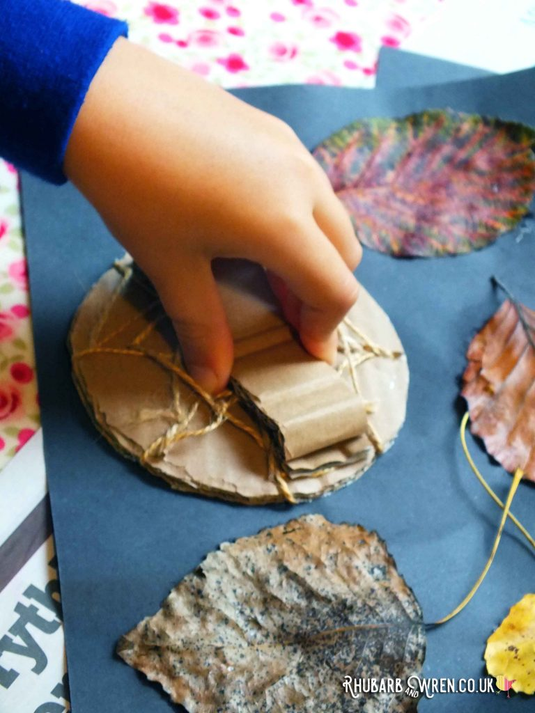 Boy's hand pressing spiderweb stamper onto leaf collage picture