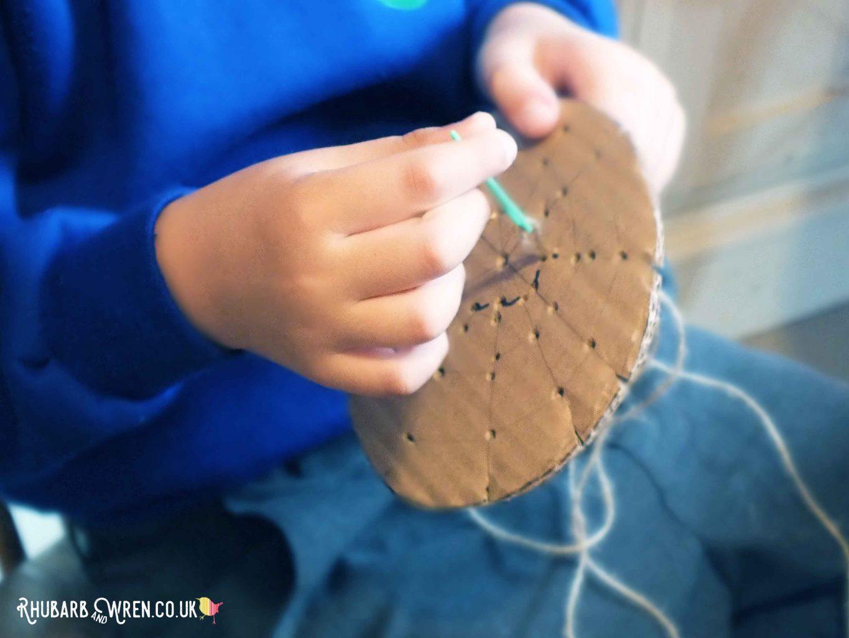 Boy threading string through spiderweb pattern using plastic needle to make spiderweb stamper