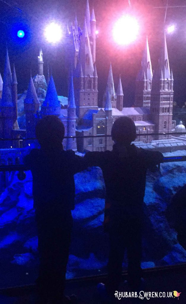 boys watching the 'sunrise' over the Hogwarts model at the Harry Potter studio tour