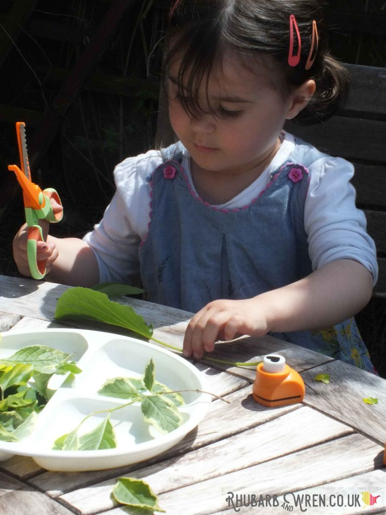 child practicing scissor skills with leaves and flowers