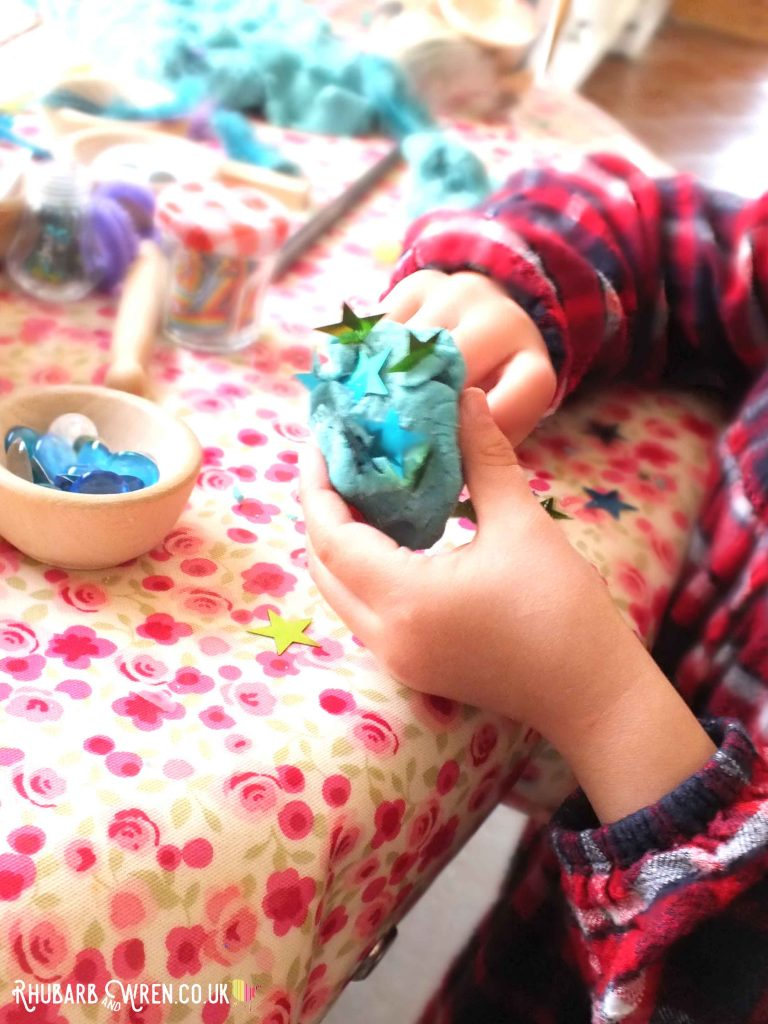 child decorating home-made play dough bog baby with sequins