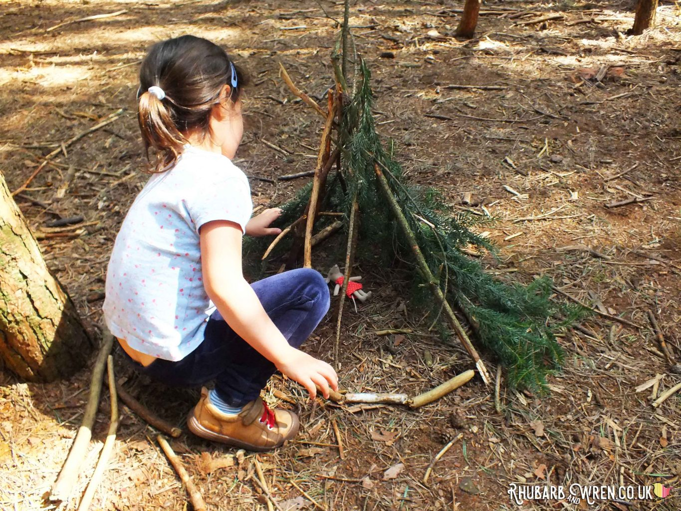 Girl adding leaves to mini den twig teepee containing Maileg mouse toy