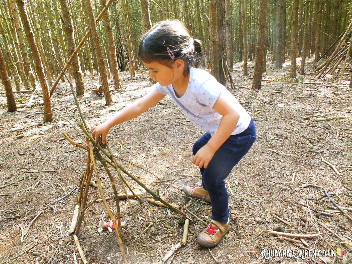 preschool girl building mini den - twig teepee in woods